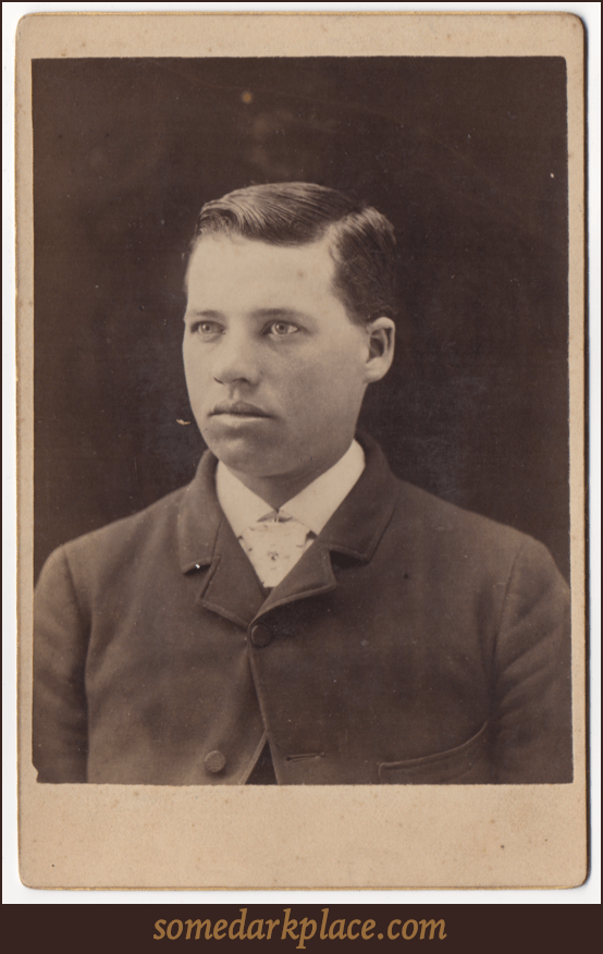 A handsome young man. He's wearing a suit coat and a white collared shirt. He appears to be wearing a tie of some sort. His hair is parted on the left.