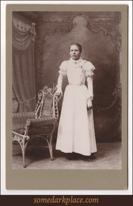 A young woman looking displeased and like she does not want her picture taken at all. She is wearing a full white gown with puffy shoulders. She also has fingerless gloves with piping on the back of the hands.