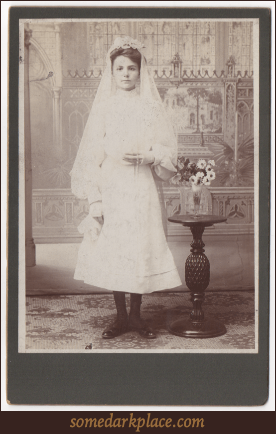 A young woman in a veil and wearing a white dress.  Most likely this is a Confirmation dress. She is holding a rosary.