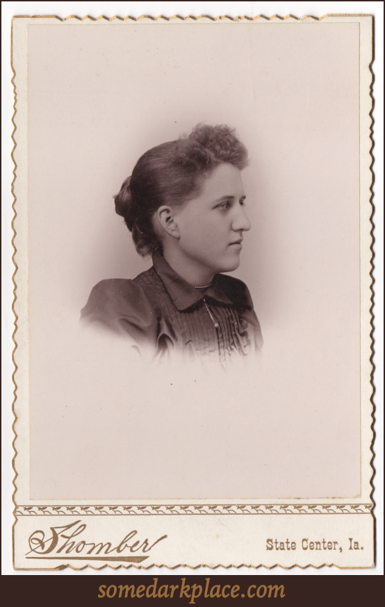 A bust image of a young woman in a dark dress or blouse with a small dangling pendant. Her hair is done in a bun at the back of the head and is loose curls in the front.
