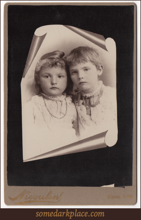 A trompe l'oeil image of two young children; one boy, one girl. Both are wearing white and have necklaces.
