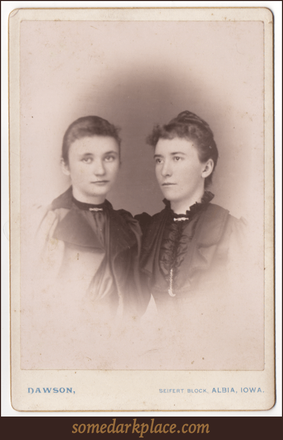 Two young women. One somewhat older that the other. Both are in partial profile. Both are wearing formal clothes with one in an overcoat and the other in a dress. Both have broaches at their necks.