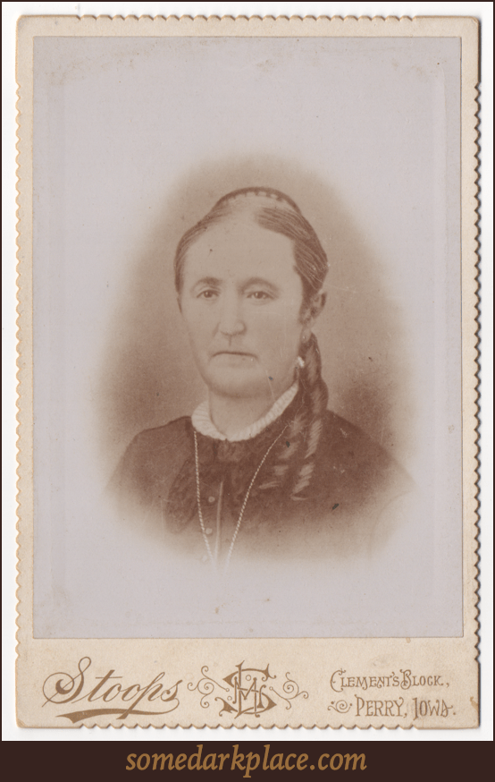 A bust of an older woman in a darker button dress or blouse. Her dress has lace ruff at the collar and she is wearing a large chain necklace (much of which cannot be seen). There appears to be some sort of bow or larger collar as well.