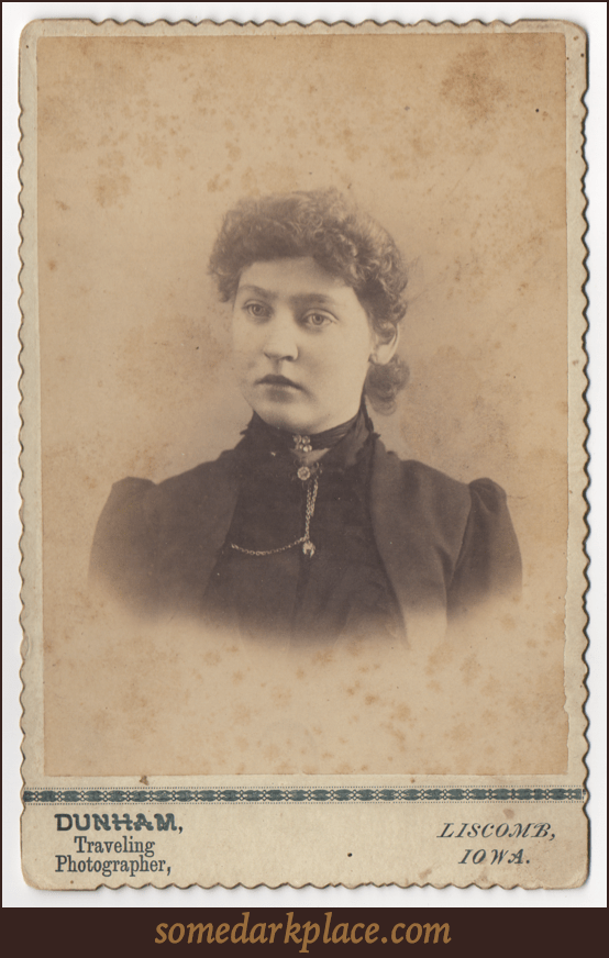 An attractive curly haired young woman with her hair pulled back. She wears both a ribbon around her throat with buttons or stones as well as an elaborate pendant with chains. She is wearing dark clothes and a sort of jacket.