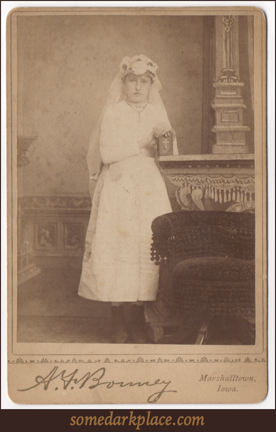 A young girl dress in a white first confession dress. These outfits have a similar appearance to wedding dresses. She is clutching a small prayer book or Bible.