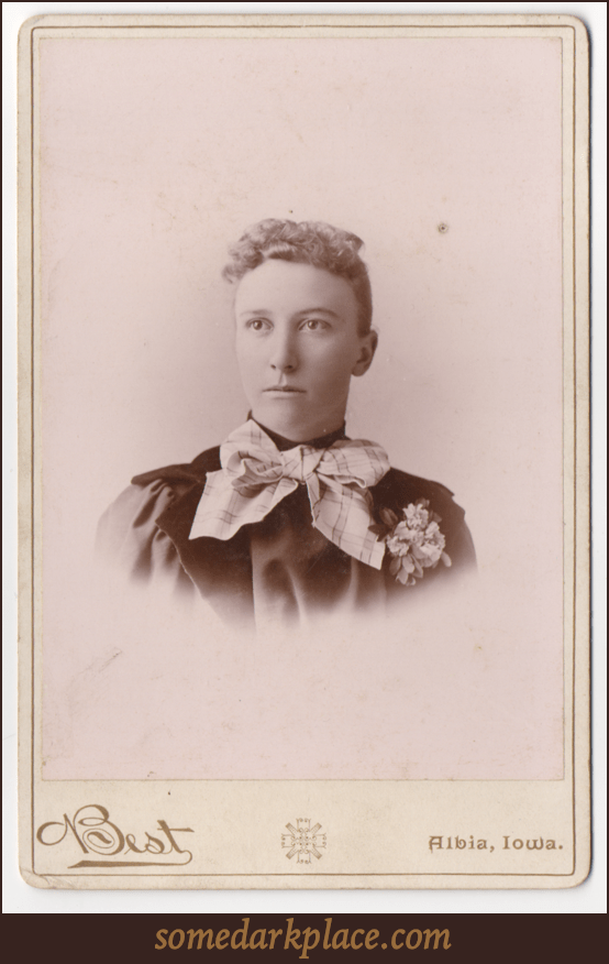 A young woman with her hair pulled back and curls in the front. She is wearing a a giant striped bow around her neck and a corsage over her heart. She is wearing a dark dress. This is a bust shot.