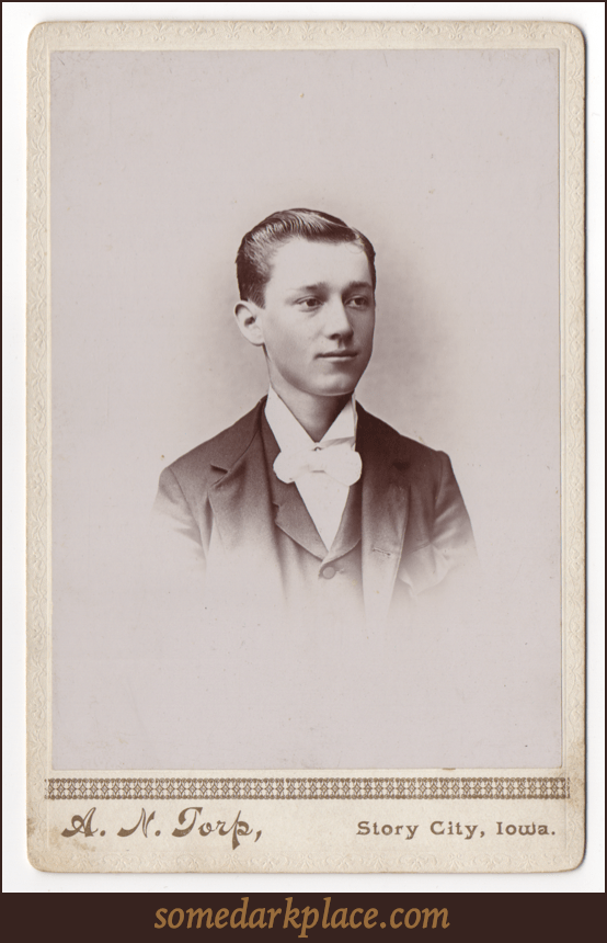 A dapper young man in formal wear. He has a dark suit and a white shirt with a large bow tie. His hair is short, parted on the left, and he has no facial hair.