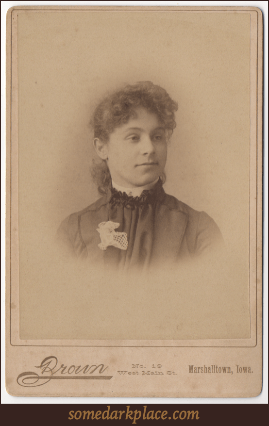 A curly haired woman with her hair swept back. She is wearing a pleated dress with a white lace flower on her lapel. She has a stiff white collar.