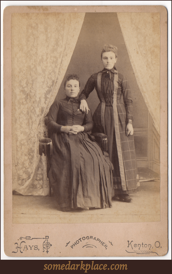Two women. One seated, the other standing with her arm resting on the other's shoulder. Both wear full length dresses with one being a simpler dark dress with buttons down the front. The other with pleats and a pattern.