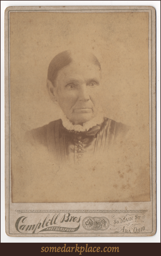 An old lady in a pleated dark dress with a frilly collar. Buttons adorn the front of the dress. Her hair is tightly pulled back and is parted down the center. The image is slightly faded, but it appeals she has pierced ears.