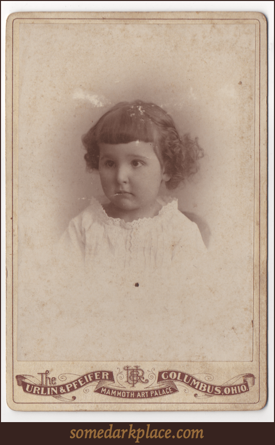 A toddler in a lacy dress or over shirt. She has short curly hair and unevenly trimmed bangs. She appears to be sitting.