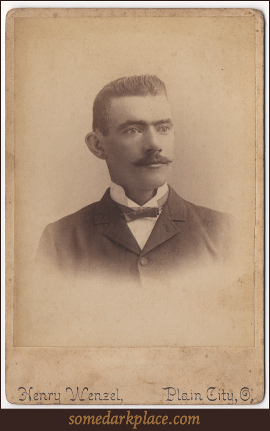 A dapper gentleman in a bowtie and a dark suit. His undershirt is light colored and his color is upturned. His hair is well groomed and short in a buzzcut style. He has a mustache that is turned up at the ends.