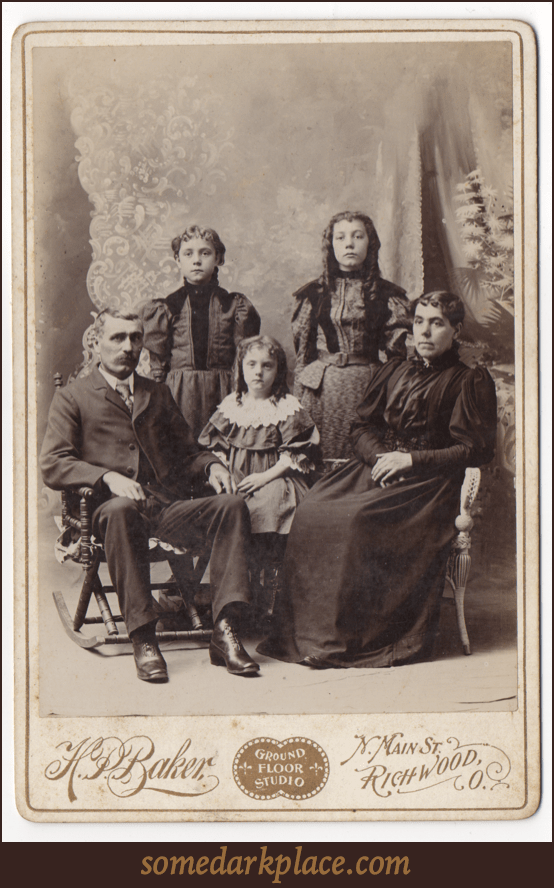 A family of five with a man, woman, and three children. All are dressed up wearing formal clothes. The adults are seated.