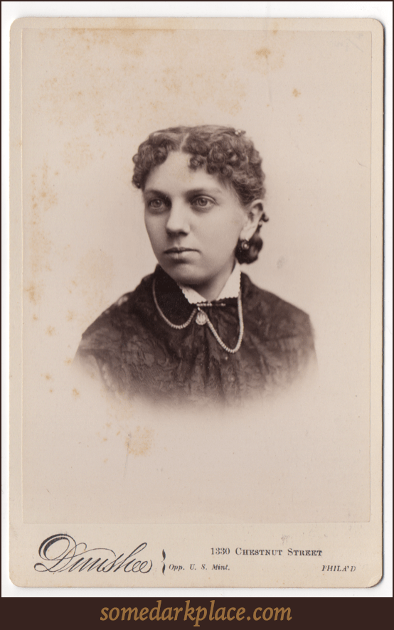 A young woman with dark curly hair parted down the middle. She is wearing a pendant style earring. She is wearing a dress with a light colored scalloped collar. She has a birch of clasp with a hanging stone and chains.