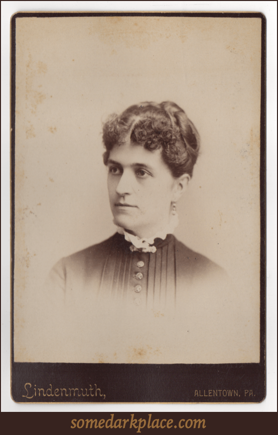 A woman with her hair piled on top of her head, pulled back, and pinned into place. She has a light colored ruffled collar, a dark pleated dress with buttons down the front, and a pendant earring. A clasp is at her throat.