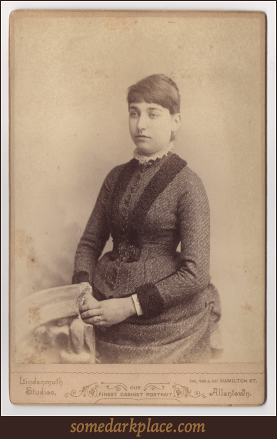 A young woman seated next to a prop stone pedestal. Her hands are filed before her. She is wearing a textured dress with a rounded and frilly collar. Her hair is pinned tightly against her head and her hair is pulled back. Her bangs are cut straight.