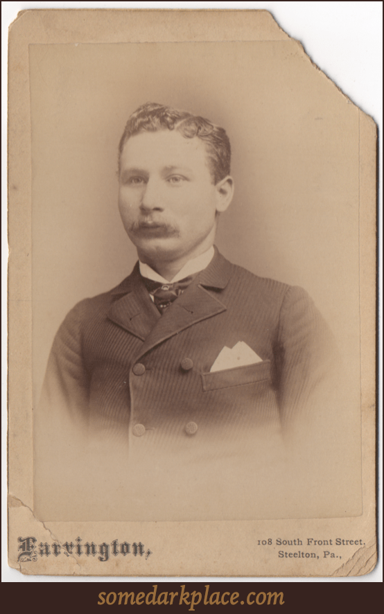 A dapper young man in a textured lined suit jacket and tie with some sort of pin through it. His hair is parted on the left and fairly short. He is looking slightly off camera. He has a mustache.