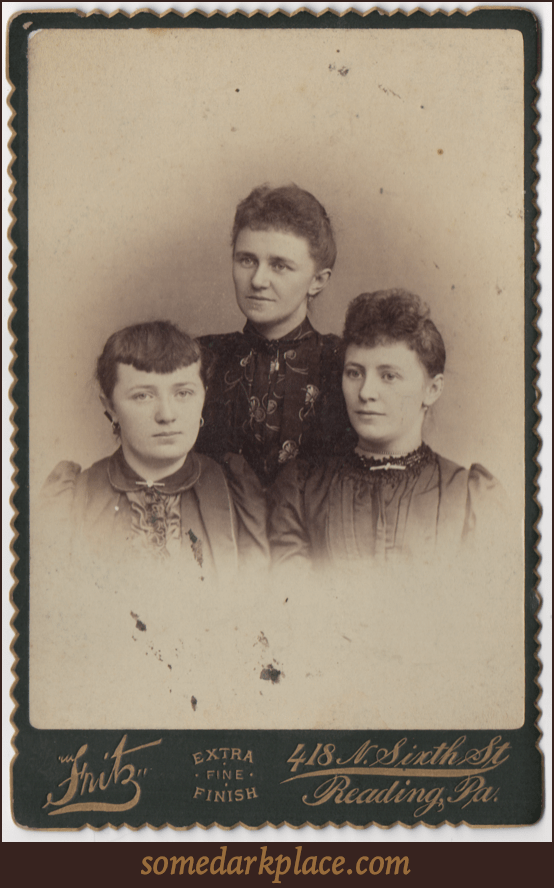 Three young women all in formal dresses. Two have hair curled in the front, one has bangs, all have their hair pulled back. All have their ears pierced and wear pendant or loop earrings. Various other pieces of jewelry are in the photo.