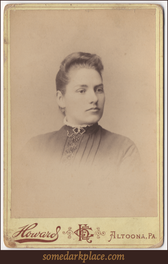 A young woman with an oval shaped face. Her hair it styled in a standing wave and is pulled back. She has a pendant earring and is wearing a rounded color trimmed in a ruffle or lace. She has a double diamond piece of jewelry as a clasp at her throat.
