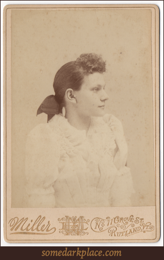 A profile of a young woman in an elaborate white dress with puffy sleeves, frills, and pleats. Her hair is curly in front and  pulled back into a large dark bow.