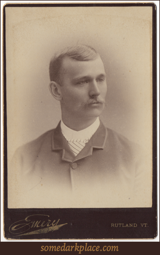 A well groomed young man with a light buttoned up suit coat and a striped tie. He is wearing a white shirt with a collar. His hair is parted on the left and is neatly trimmed. He sports a longer mustache.