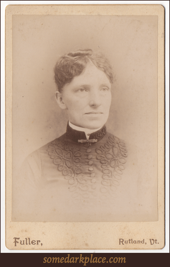An older woman with her wavy hair pinned to her head and pulled back. She is wearing a dark dressed adorned with elaborate piping on either side of a centerline of large matching buttons. She has a white round collar. There is a clasp at her throat.