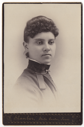 An attractive young woman in a high collared smock or dress. She is wearing a choker style necklace on the outside of the collar with a metal clasp at her throat. She is also wearing a broach on her left side.
