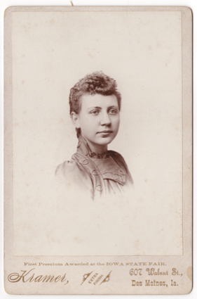 A headshot of an attractive young woman perhaps in her late teens. She is wearing a dress with a high collar and elaborate decorative piping. Her hair is curly in the front and pulled back or short.
