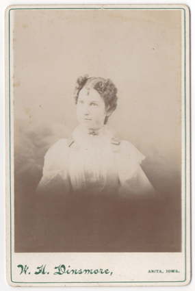 A young woman with a severe part down the middle of her head. She is wearing all white. She has decorative buckles or ribbons on her shoulders and a broach at her throat.