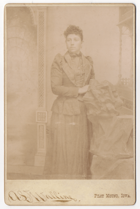A young woman in a full length dress. This is an obvious studio shot with a prop rock and a painted background.