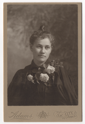 A beautiful young woman with her hair in a topknot and pulled back. She is wearing a dark dress and perhaps an overcoat or cloak. Her outfit is embellished with four large white roses and leaves.
