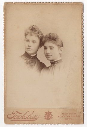 Two young women. Both in partial profile. Both are wearing dresses. One has a broach and the other a clasp at her throat. They wear high collars with white trimming.