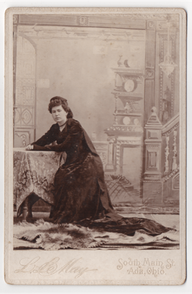 An obvious studio shot of a younger woman in dark flowing garb. She is wearing a headdress and has a cover around her throat. Her hair is curly, parted on the left, and pinned back. She sits at a prop table in front of a painted background.