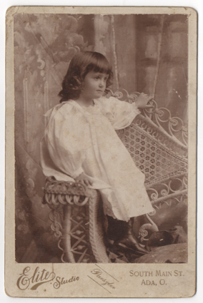 A young girl in an all white dress and black boots. She has long hair that is curly on the ends, but otherwise hangs straight down. She is seated in a whicker chair in a studio in front of a painted backdrop.