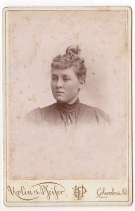 A curly haired young woman with her hair pulled up into a topknot. It appears there is a bow in her hair or some other ornament. She has round cheeks and her ears are pierced.