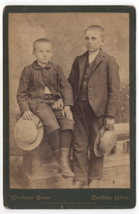 Two young boys sitting on a stone railing in front of a painted background in a studio shot. Both are holding stew hats with ribbons around the brim. One child is older than the other by a year or two.