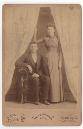 A young couple. The man is seated, the woman stands at his right to the left. Her hand is holding onto a curtain. They are both wearing formal wear. This photo is a studio shot.