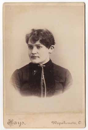 A young woman with short unkempt hair. She has a masculine appearance. She wears a top with buttons and piping down the front. She has a clasp at her throat and another pice of ornamental jewelry.