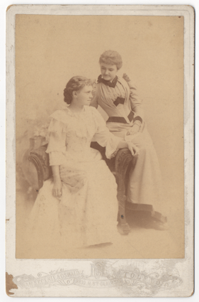 Two attractive young women. One fully seated and the other leaning into the armrest of this chair. One woman is looking at the other affectionately. Both women are wearing formal dresses.