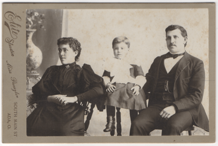 A small family: husband, wife, and son (presumably). The man is in a suit, the woman in a full length dress, and the boy still in a dress (not yet in breaches).