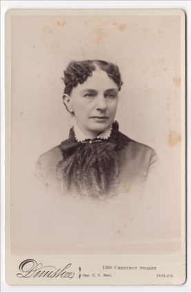 A woman with dark curly hair parted down the middle. She is wearing a pendant style earring. She is wearing a dress with a light colored scalloped collar. She has a clasp at her throat. She has a scarf or decorative cloth going down the front of her dress.