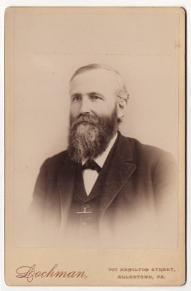 An older bearded gentleman wearing a suit coat and undershirt. He is wearing a dark tie of some sort. He has a watch chain or some other functional appealing jewelry. His beard and hair are starting to gray.