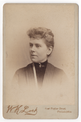 A woman with her hair pinned back and piled atop her head. Her bangs are curly and she looks like she would have a lot of hair to let down if she were so inclined. Her collar is rounded and dark and she has a piece of jewelry of some sort at her neckline.