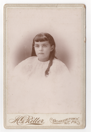 A young girl in a white robe or smock. Could be a sleeping shirt or more likely a dress. Her hair is long with some curl to it. Her bangs are neatly trimmed and even. Most her hair falls down her back, but one curled strand sits on her shoulder.