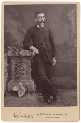 A man in a full dark suit leaning against a prop of a garden wall. He has on a light colored dress shirt and dark shoes with a shine to them. His mustache is large and impressive and well groomed.
