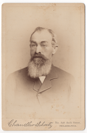 An older bearded gentleman wearing a suit coat and undershirt. He does not appear to be wearing a tie, but this could be obscured by his beard.