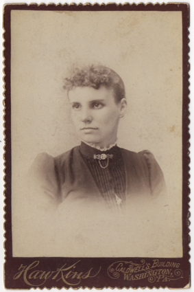 A curly haired young woman with a high collared dress with lace trim and a clasp and chain at her throat. Her dress is pleated in the front and has a piece of jewelry hanging in the front.
