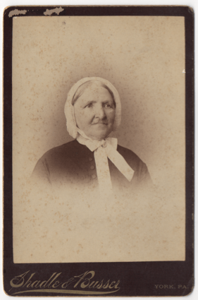 A old woman in a bonnet tied in a bow around her neck. Some sort of broach or clasp is at the center of the bow. Her gray hair is pulled back, parted down the middle, and mostly covered. She is wearing a dark frock with large buttons down the center.