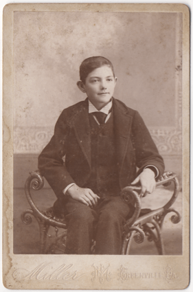 A young boy seated in an elaborate chair or bench without a back. He is dressed in formal attire, wearing a suit coat and tie. His hair is short, trimmed, and neatly combed. His ears stick out.