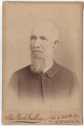 An older gentleman with white facial hair. The image has either faded or has exposure issues, so is difficult to tell if he is bald or just has shorter white hair. He is wearing a simple overcoat with a lighter shirt peaking out.